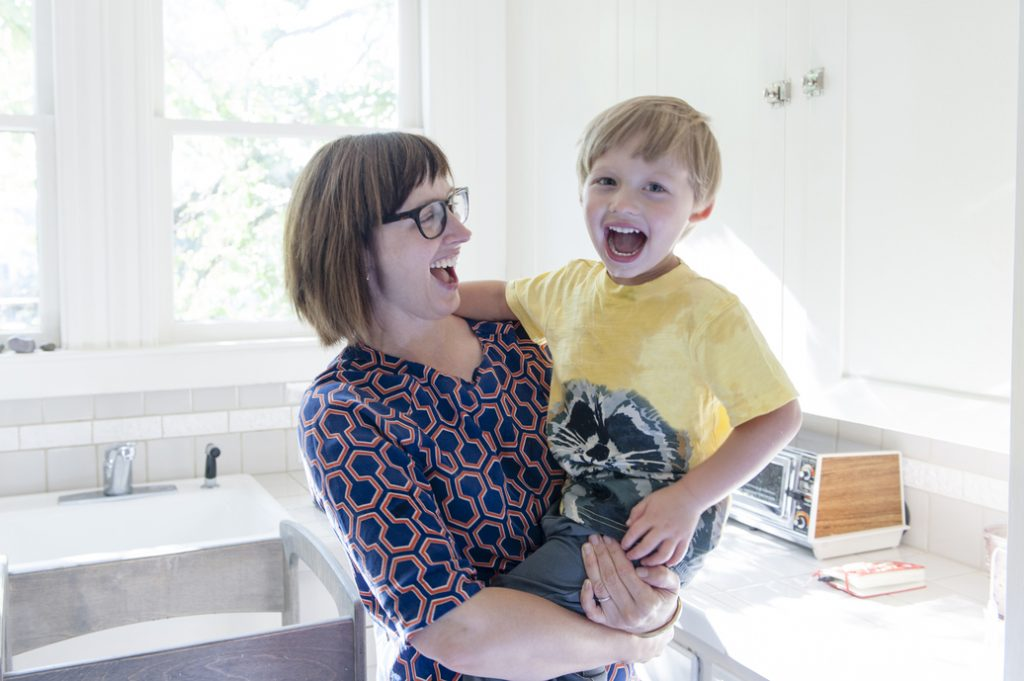 Mother holding son in kitchen